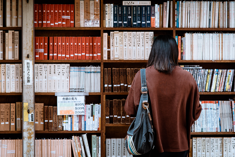 Woman Wearing Brown Shirt In Front Of Books